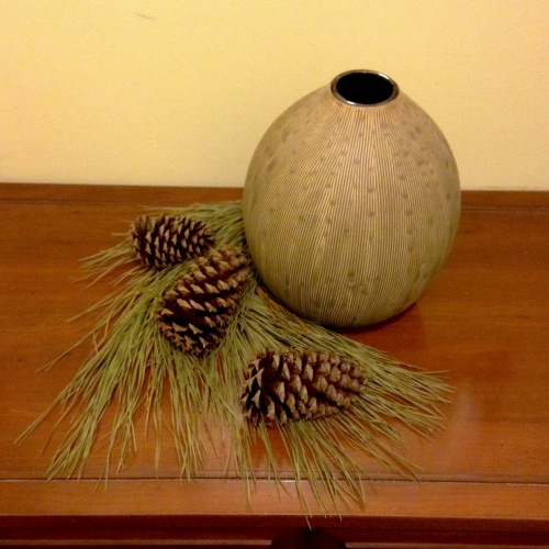 Vase with pine needles and cones