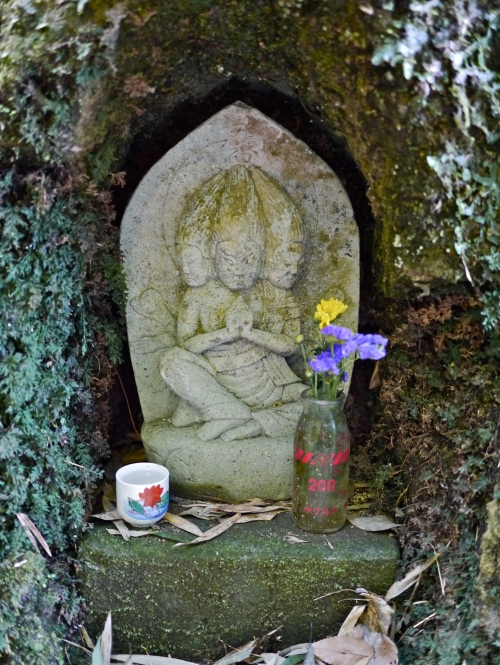 Small statue along the path, with flower offerings.