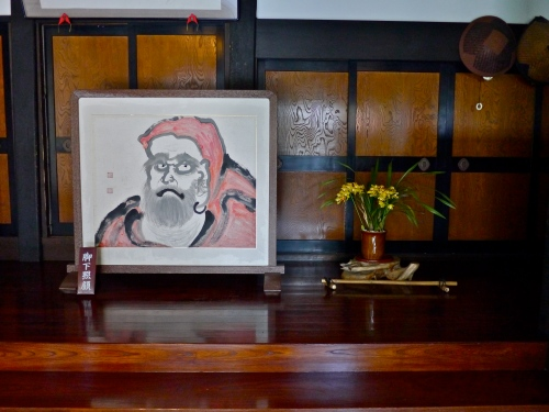 Brush painting of Daruma (Bodhidharma) and flowers in the genkan of the main entrance.