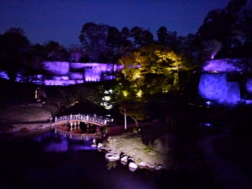 Kanazawa Castle garden with purple-lighted walls.