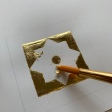 A decorative square to practice laying gold leaf.