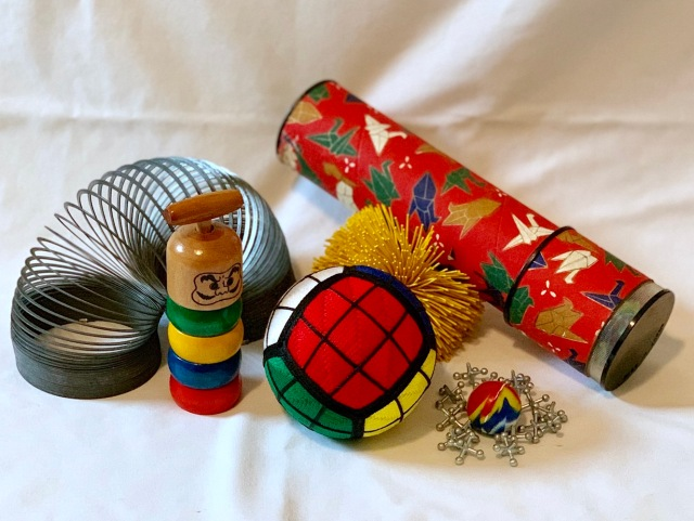 The completed Rubik's cube temari staged with other children's toys